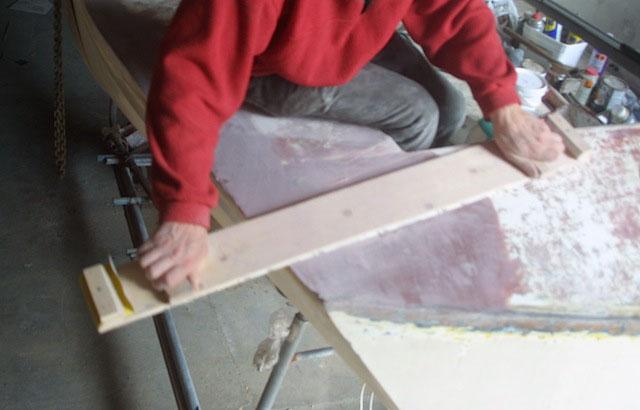 Usando una tabla de lijado para preparar una zona de la cubierta para la pintura.