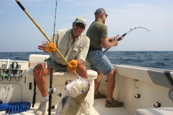 dos hombres pescando en barco